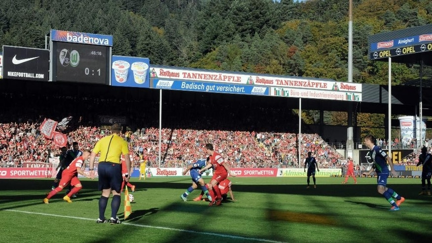 In this photo taken Saturday, Oct. 18, 2014, Freiburg, playing in red, face Wolfsburg in a Bundesliga soccer match in Freiburg, Germany. As one of the Bundesliga's most financially disadvantaged teams, Freiburg deploys an array of coping strategies to stay in Germany's top division and remain competitive against rivals like Wolfsburg that have richer resources, revenues and budgets. (AP Photo/John Leicester)