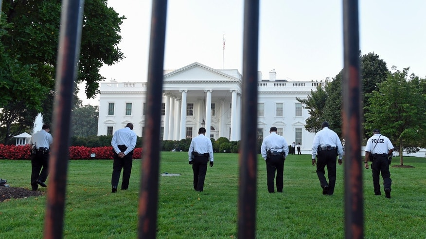 FILE - In this Sept. 20, 2104 file photo uniformed Secret Service officers walk along the lawn on the North side of the White House in Washington, Saturday, Sept. 20, 2014. The Secret Service is coming under intense scrutiny after a man who hopped the White House fence made it all the way through the front door before being apprehended. The US Secret Service and National Park Service have been discussing possible changes to the security infrastructure on roads and parks around the White House. The Secret Service is deciding whether to permanently close the Ellipse and other roadways, which have been closed since 9/11.(AP Photo/Susan Walsh, File)