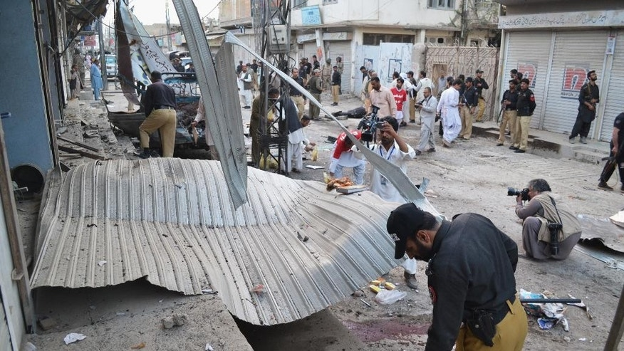 Pakistani investigators collect evidence from the site of a suicide bombing in Quetta, Pakistan, Thursday, Oct. 23, 2014. A suicide bomber detonated his explosives next to a bullet proof car carrying Maulana Fazlur Rehman, the chief of Taliban-linked Jamiat Ulema-e-Islam religious party, said Baluchistan police chief Amlesh Khan. Quetta city is the capital of Baluchistan province. Rehman survived the attack, that killed at least two people and wounded several others, he said. (AP Photo/Arshad Butt)
