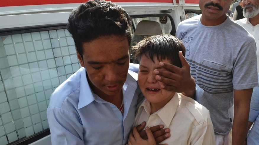 A man from Pakistan's minority Shiite Hazara community comforts a child who lost his family member in an attack by four gunmen in Quetta, Pakistan, Thursday, Oct. 23, 2014. The four gunmen riding two motorcycles attacked a minibus carrying Shiite Muslims in southwestern Pakistan followed by two deadly bomb blasts on Thursday. (AP Photo/Arshad Butt)