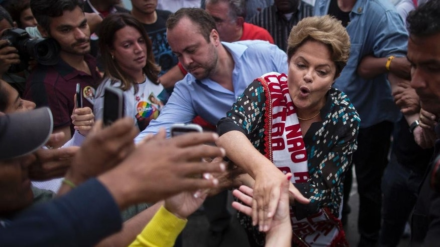 Dilma Rousseff, Brazil's president and Workers Party candidate, greets supporters as she campaigns for re-election at a rally in Duque de Caxias on the outskirts of Rio de Janeiro, Brazil, Wednesday, Oct. 22, 2014. Rousseff is in a tight election contest that culminates Oct. 26 when Brazilians are expected to go to the polls and decide who'll be the next leader of Latin America's biggest economy. (AP Photo/Felipe Dana)