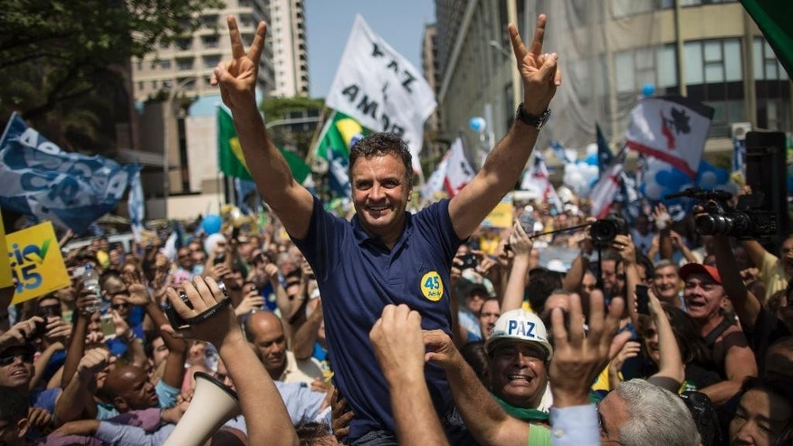 Aecio Neves, Brazilian Social Democracy Party presidential candidate, greets supporters while campaigning at Copacabana beach in Rio de Janeiro, Brazil, Sunday, Oct. 19, 2014.  Neves will face Brazil's President Dilma Rousseff in a presidential runoff on Oct. 26. (AP Photo/Felipe Dana)