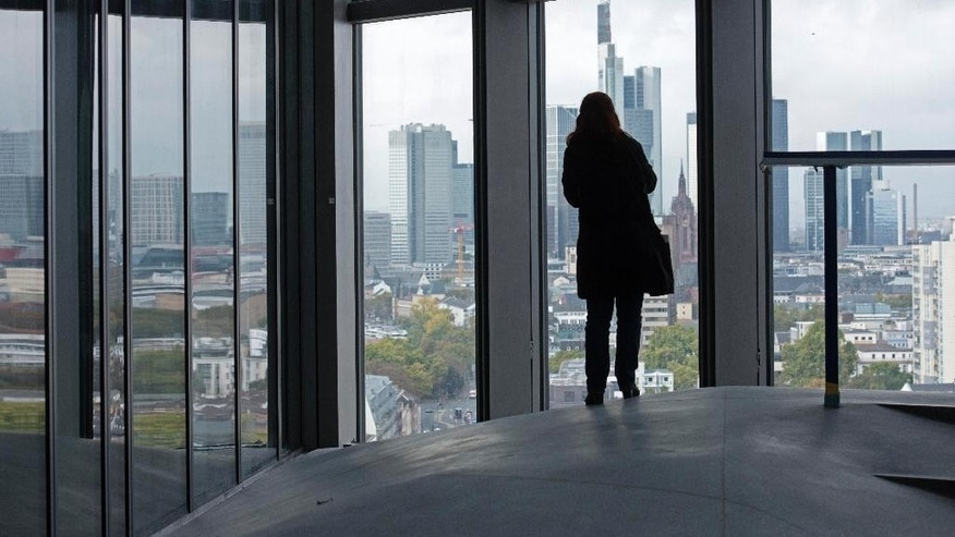 A woman stands in front of a window in the new headquarters of the European Central Bank during a media tour at the construction site in Frankfurt, Germany, Tuesday, Oct. 21, 2014. The ECB is supposed to move into the building by the end of 2014. (AP Photo/Jens Meyer)