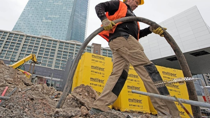 A worker is busy  in front of the new headquarters of the European Central Bank during a media tour at the construction site in Frankfurt, Germany, Tuesday, Oct. 21, 2014. The ECB is supposed to move into the building by the end of 2014. (AP Photo/Jens Meyer)