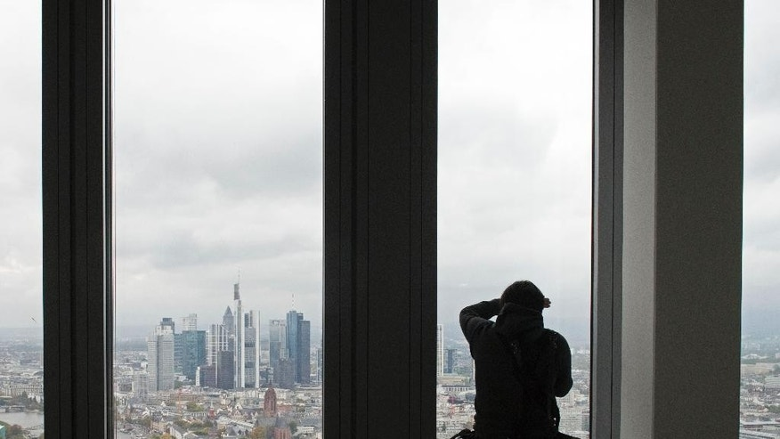 A journalist takes pictures  in the council meeting room in the 41.  floor,  at  the new headquarters of the European Central Bank during a media tour at the construction site in Frankfurt, Germany, Tuesday, Oct. 21, 2014. The ECB is supposed to move into the building by the end of 2014.  (AP Photo/Jens Meyer)