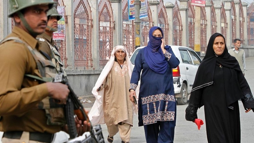 Indian paramilitary soldiers stand guard as Kashmiri women walk on a street in Srinagar, India, Thursday, Oct. 23, 2014. Shops and businesses remained closed in Kashmir due to a separatist sponsored strike to protest a visit to the region by Prime Minister Narendra Modi. (AP Photo/Mukhtar Khan)
