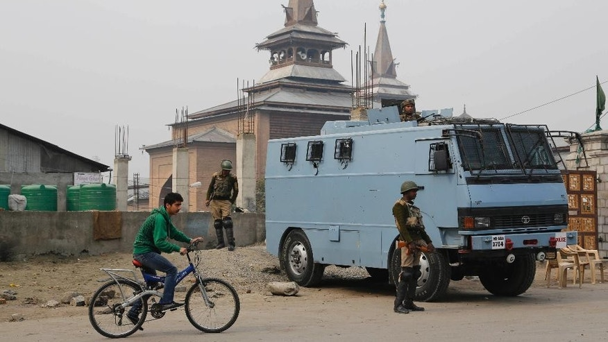A Kashmiri boy rides bicycle past Indian paramilitary soldiers keeping guard outside Jamia Masjid in Srinagar, India, Thursday, Oct . 23, 2014. Shops and businesses remained closed in Kashmir due to a separatist sponsored strike to protest a visit to the region by Prime Minister Narendra Modi. (AP Photo/Mukhtar Khan)