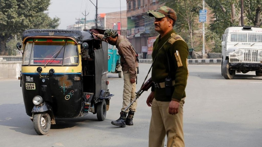 Indian policemen check passing vehicles on a street in Srinagar, India, Thursday, Oct. 23, 2014. Shops and businesses remained closed in Kashmir due to a separatist sponsored strike to protest a visit to the region by Prime Minister Narendra Modi. (AP Photo/Mukhtar Khan)