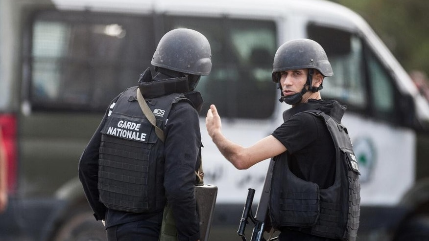 Members of the Tunisian National Guard take positions as they secure the scene of a shooting in the Oued Ellil suburb of Tunis, Tunisia, Thursday, Oct. 23, 2014. A Tunisia official says a security officer has been killed in a shootout that began when a suspect's home was surrounded near the capital. Interior Ministry spokesman Mohammed Ali Aroui says the exchange of fire Thursday came after a pair of counterterrorism operations in the south that left one bystander dead. (AP Photo/Aimen Zine)