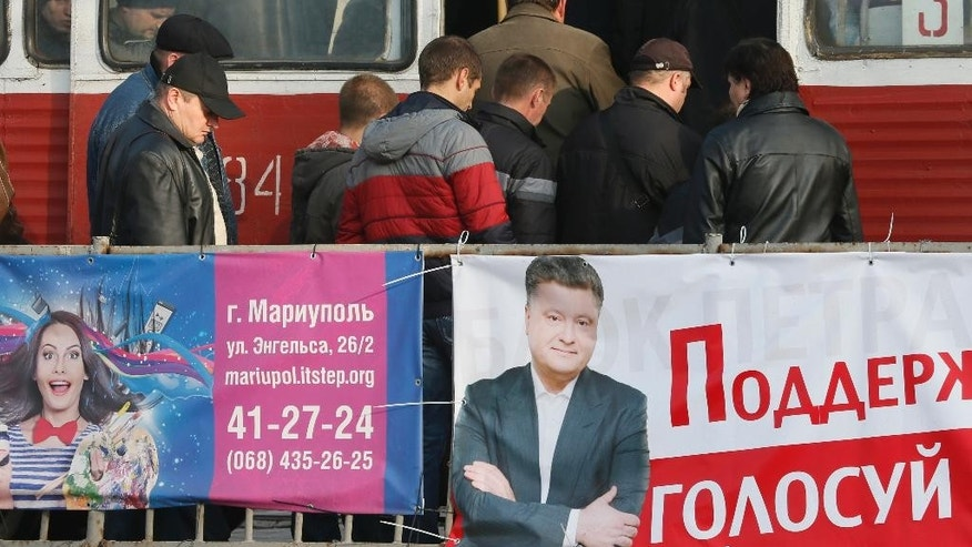 People board a tram near an election poster depicting Ukraine's President Petro Poroshenko, right, in the town of Mariupol, eastern Ukraine Wednesday, Oct. 22, 2014. Ukraine's parliament elections are scheduled for Sunday Oct. 26. (AP Photo/Dmitry Lovetsky)