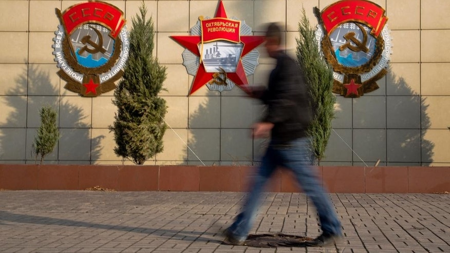 A man walks past Soviet era emblems  hanging on a wall near an entrance to the Azov steel factory in the Ukrainian government controlled town of Mariupol, eastern Ukraine Wednesday, Oct. 22, 2014. Ukrainian parliamentary elections are on Sunday. (AP Photo/Dmitry Lovetsky)
