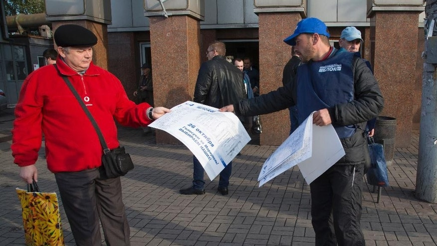 A man distributes flyers of candidates for the parliament elections in the Ukrainian government controlled town of Mariupol, eastern Ukraine Wednesday, Oct. 22, 2014. Ukraine's parliament elections are scheduled on Sunday, Oct. 26 .  (AP Photo/Dmitry Lovetsky)