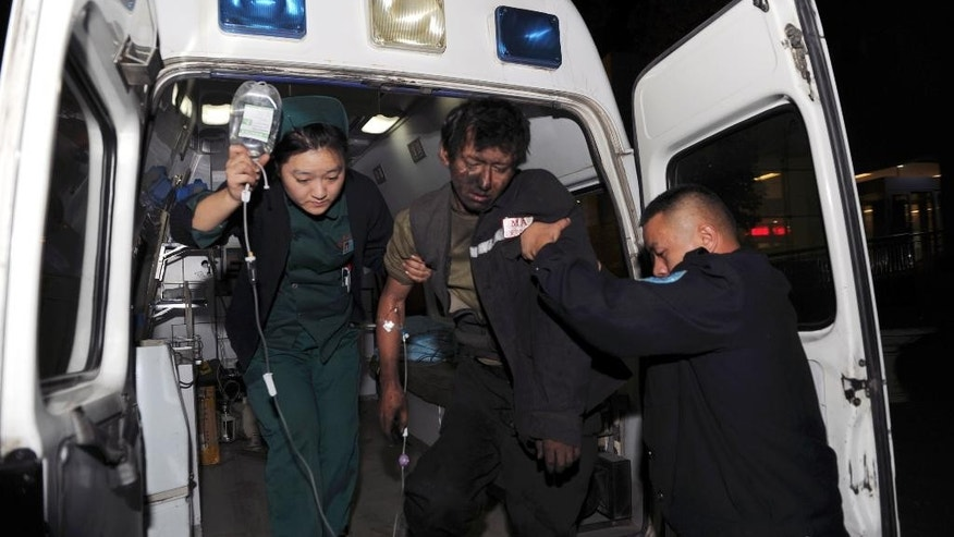 In this photo provided by China's Xinhua News Agency,   an injured miner is transferred to hospital after a coal mine collapsed in Tiechanggou township,  China's Xinjiang  regional capital of Urumqi Saturday, Oct. 25, 2014. China's official news agency says 16 coal miners were killed after their shaft collapsed in the country's northwest.  (AP Photo/Xinhua, Zhao Ge) NO SALES
