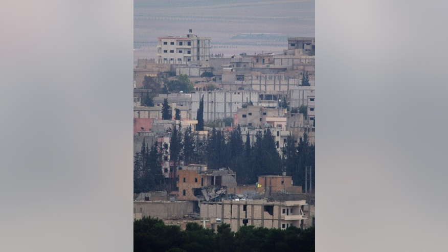 The proximity of the Islamic State group to the Kurdish forces defending the Syrian border town of Kobani is seen with the yellow triangular flag of the Kurdish People's Protection Units, or YPG, flying on a building, bottom right, just inside Kobani in Syria, near the Turkey-Syria border Thursday, Oct. 23, 2014. In the background, the black flag of the Islamic State group flies atop a building, top left, Kobani, also known as Ayn Arab, and its surrounding areas, has been under assault by extremists of the Islamic State group since mid-September and is being defended by Kurdish fighters. (AP Photo/Lefteris Pitarakis)