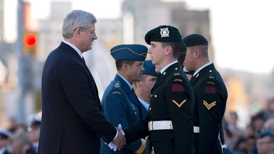 Canadian Prime Minister Stephen Harper, left, and General Tom Lawson, Chief of the Defence Staff of the Canadian Armed Forces, centre, take part in a ceremony to return ceremonial guards to the Tomb of the Unknown Soldier at the National War Memorial in Ottawa on Friday, Oct. 24, 2014. The sentries returned to their posts two days after Cpl. Nathan Cirillo, 24, a reservist from Hamilton, Ont., was killed by a gunman while guarding the tomb, who then moved to nearby Parliament Hill, opening fire before he himself was shot dead.  (AP Photo/The Canadian Press, Justin Tang)