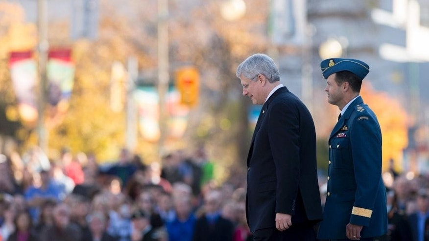 Canadian Prime Minister Stephen Harper, left, and General Tom Lawson, Chief of the Defence Staff of the Canadian Armed Forces, take part in a ceremony to return ceremonial guards to the Tomb of the Unknown Soldier at the National War Memorial in Ottawa on Friday, Oct. 24, 2014. The sentries returned to their posts two days after Cpl. Nathan Cirillo, 24, a reservist from Hamilton, Ont., was killed while guarding the tomb by a gunman, who then moved to nearby Parliament Hill, opening fire before he himself was shot dead.  (AP Photo/The Canadian Press, Justin Tang)