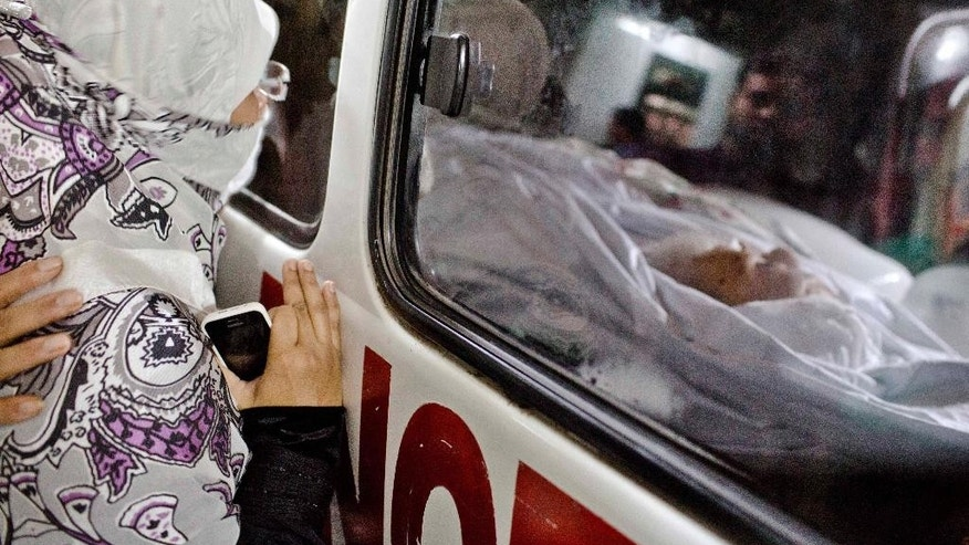 A woman watches the body of her relative and Bangladesh's Islamic party Jamaat-e-Islami's former leader Ghulam Azam in an ambulance outside his home in Dhaka, Bangladesh, Friday, Oct. 24, 2014. Azam, 91, whose imprisonment on war crimes charges triggered violent protests last year, died late Thursday of a heart attack in a prison cell of a government hospital. (AP Photo/A.M. Ahad)
