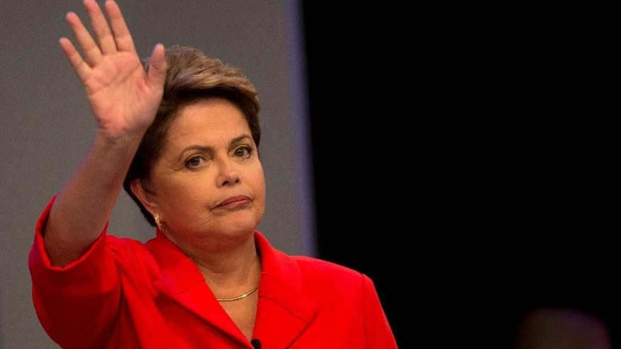 Brazil's incumbent President and Workers Party presidential candidate Dilma Rousseff, greets the audience as she arrives on stage for the start of a presidential debate with challenger Aecio Neves, presidential candidate of the Brazilian Social Democracy Party, in Rio de Janeiro, Brazil, Friday, Oct. 24, 2014. Rousseff and Neves are in a tight election contest, that culminates Sunday when millions of Brazilians are expected to go to the polls and decide who'll be the next leader of Latin America's biggest economy. (AP Photo/Silvia Izquierdo)
