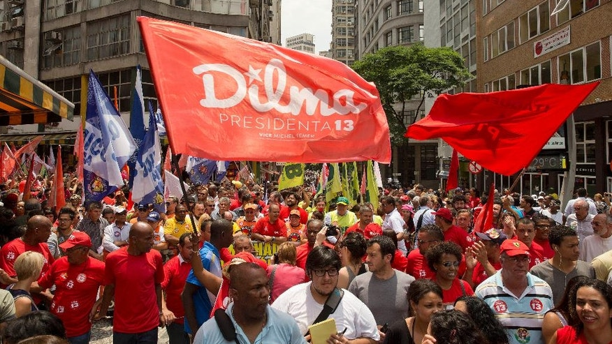 Supporters of Brazil's President Dilma Rousseff, who's running for re-election with the Workers Party (PT), rally in Sao Paulo, Brazil, Friday, Oct. 24, 2014. Voters will decide on Sunday who'll be the next leader of Latin America's biggest economy. (AP Photo/Andre Penner)
