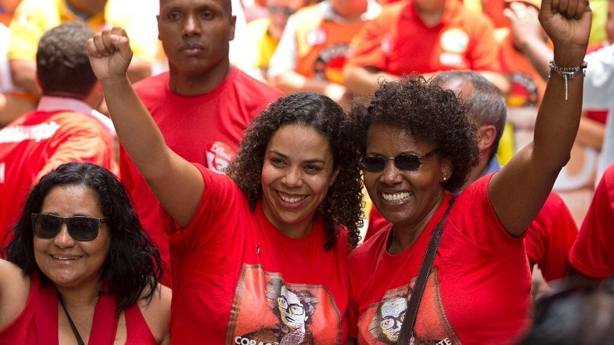 Women pose for pictures as they campaign for Brazil's President Dilma Rousseff, who's running for re-election with the Workers Party (PT), at a rally in Sao Paulo, Brazil, Friday, Oct. 24, 2014. Voters will decide on Sunday who'll be the next leader of Latin America's biggest economy. (AP Photo/Andre Penner)