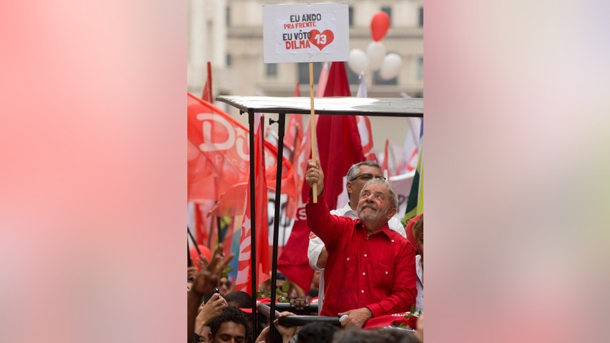 "Brazil's former President Luiz Inacio Lula da Silva holds up a sign that reads in Portuguese ""I walk forward, I vote for Dilma"" at a campaign rally for Brazil's President Dilma Rousseff who's running for re-election with the Workers Party (PT) in Sao Paulo, Brazil, Friday, Oct. 24, 2014. Voters will decide on Sunday who'll be the next leader of Latin America's biggest economy. (AP Photo/Andre Penner)"