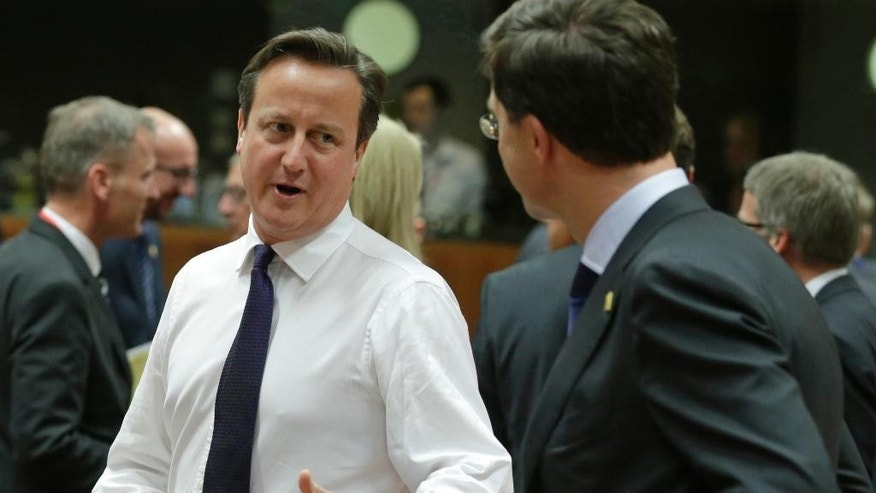 British Prime Minister David Cameron, center, speaks with Dutch Prime Minister Mark Rutte during a round table meeting at an EU summit in Brussels, on Thursday, Oct. 23, 2014. EU leaders will gather Thursday for a two-day summit in which they will discuss Ebola, climate change and the economy. (AP Photo/Yves Logghe)