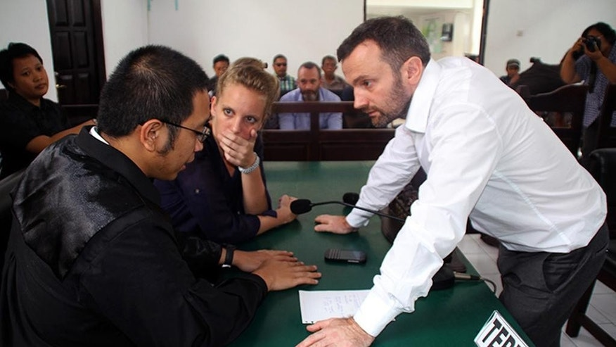 French journalists Valentine Bourrat, center, and Thomas Dandois, right, consult with their lawyer during their trial hearing in Jayapura, Papua province, Indonesia, Friday, Oct. 24, 2014. The two French television journalists were sentenced to two and a half months in jail Friday for illegal reporting in Indonesia's easternmost province of Papua. (AP Photo/Djefri Pattirajawane)