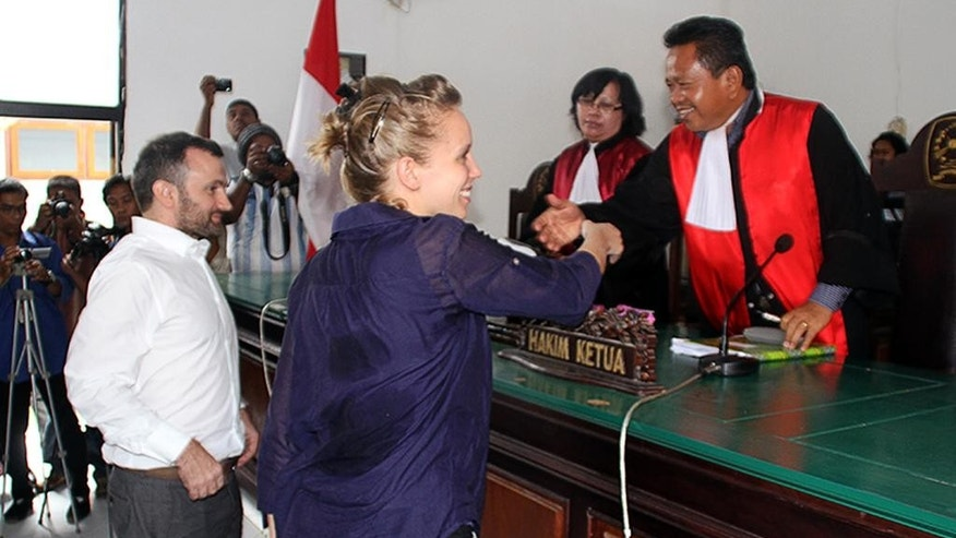 French journalists Valentine Bourrat, center, and Thomas Dandois are about to shake hands with the judges during their trial hearing in Jayapura, Papua province, Indonesia, Friday, Oct. 24, 2014. The two French television journalists were sentenced to two and a half months in jail Friday for illegal reporting in Indonesia's easternmost province of Papua. (AP Photo/Djefri Pattirajawane)