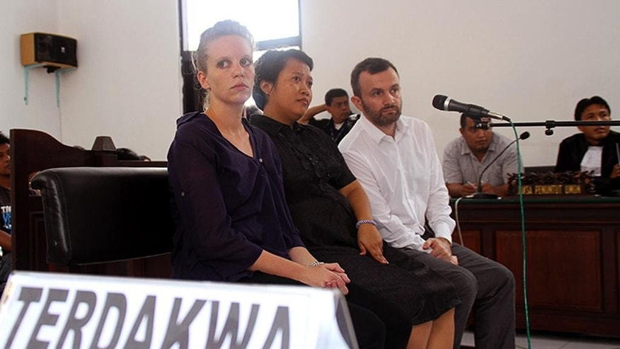 "French journalists Valentine Bourrat, left, and Thomas Dandois sit on the defendant's chair with their unidentified interpreter, center, during their trial hearing in Jayapura, Papua province, Indonesia, Friday, Oct. 24, 2014. The two French television journalists were sentenced to two and a half months in jail Friday for illegal reporting in Indonesia's easternmost province of Papua. Writing on the table reads: ""Defendant."" (AP Photo/Djefri Pattirajawane)"