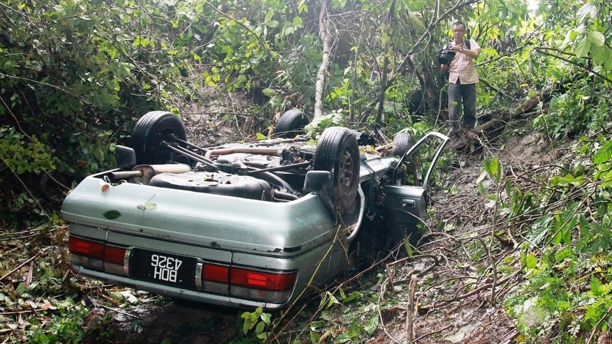 In this Oct. 23, 2014 photo, a car driven by a man identified as Nicholas Andrew is seen overturned at a jungle in Tapah, Perak state, Malaysia. Andrew seriously injured in the car accident crawled through jungle for three days before happening upon an isolated village, authorities said Friday. (AP Photo) MALAYSIA OUT