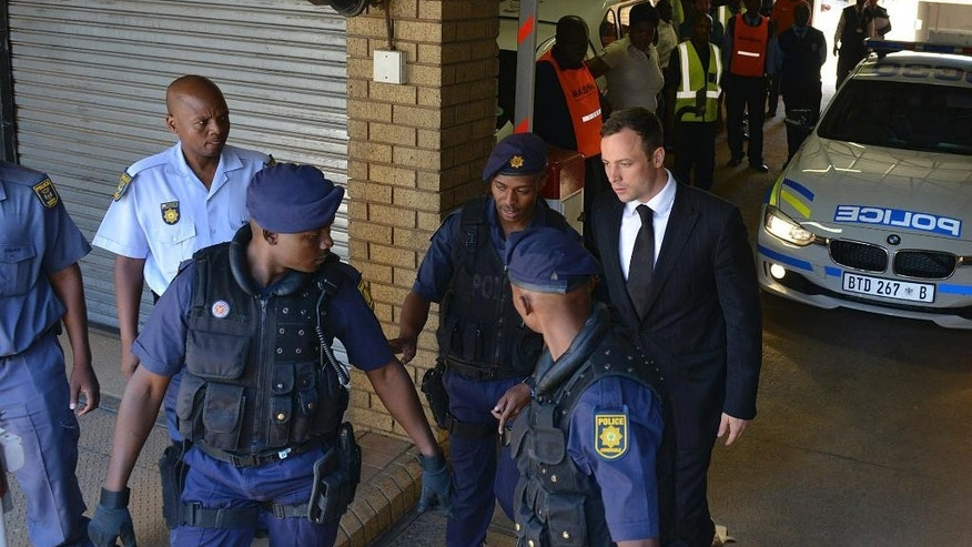 Oscar Pistorius, rear right, is led to a awaiting police vehicle to be taken to prison outside the court in Pretoria, South Africa, Tuesday, Oct. 21, 2014. Pistorius was handed down a five-year sentence by judge Thokozile Masipais for killing his girlfriend Reeva Steenkamp last year.  (AP Photo/Antoine de Ras, Independent Newspapers)  SOUTH AFRICA OUT