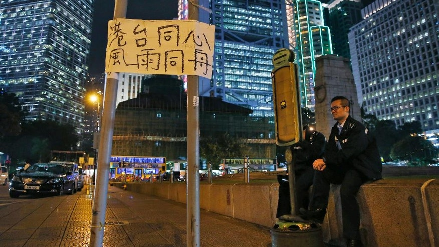 "Police officers sit next to a placard reads ""Hong Kong and Taiwan share with one heart through thick and thin"" at the occupied area in Central of Hong Kong Thursday, Oct. 23, 2014. As thousands of protesters block city streets demanding democratic reforms, the future of Hong Kong's exclusive — some would say purposefully opaque — election committee may prove key to defusing a high-stakes political standoff that has dragged on for nearly a month. (AP Photo/Kin Cheung)"