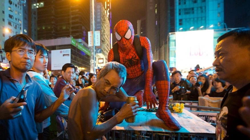 A pro-democracy protester dressed as Spider-man, looks at a drunken anti-occupied supporter at a barricade in the occupied area in the Mong Kok district of Hong Kong, Friday, Oct. 24, 2014. Pro-democracy protesters in Hong Kong plan to hold a spot referendum Sunday on whether to stay in the streets or accept government offers for more talks and clear their protest camps. (AP Photo/Kin Cheung)
