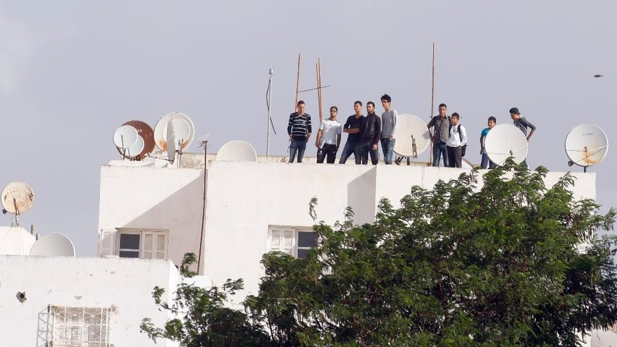 Tunisian youths stand on a roof as they watch ongoing police operations following a shooting with militants in the Oued Ellil suburb of Tunis, Tunisia, Thursday, Oct. 23, 2014. A Tunisia official says a security officer has been killed in a shootout that began when a suspect's home was surrounded near the capital. Interior Ministry spokesman Mohammed Ali Aroui says the exchange of fire Thursday came after a pair of counterterrorism operations in the south that left one bystander dead. (AP Photo/Aimen Zine)