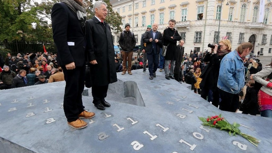 German artist Olaf Nicolai and Austrian President Heinz Fischer, from left, stand on a memorial dedicated to deserters of the Nazi Wehrmacht troops and victims of their military justice during its unveiling ceremony in downtown Vienna, Austria, Friday, Oct. 24, 2014. The memorial is located in front of the presidential office in the Hofburg palace and the federal chancellery, background. (AP Photo/Ronald Zak)