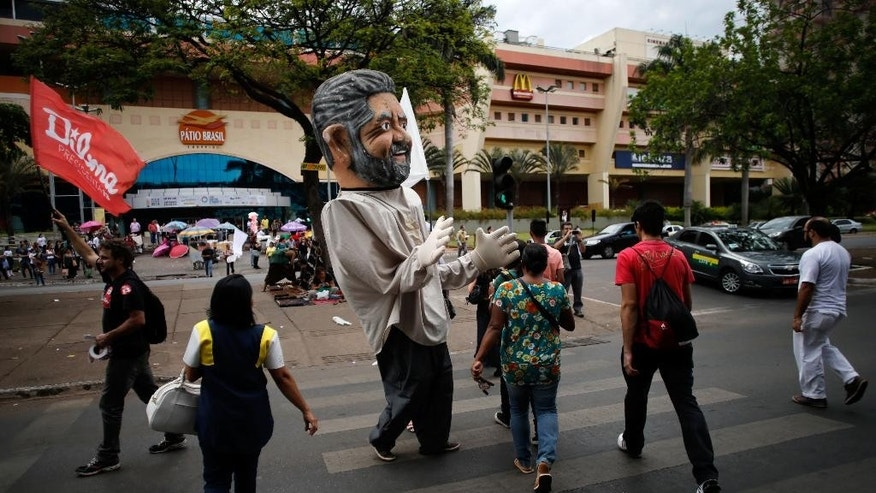 A giant puppet in the likeness of Brazil's former President Luiz Inacio Lula da Silva dances on the street in support of incumbent President Dilma Rousseff, in Brasilia, Brazil, Friday, Oct. 24, 2014. Rousseff and challenger Aecio Neves, the presidential candidate for the Brazilian Social Democracy Party, are in a tight election contest, that culminates Oct. 26 when millions of Brazilians are expected to go to the polls and decide who'll be the next leader of Latin America's biggest economy.  (AP Photo/Eraldo Peres)