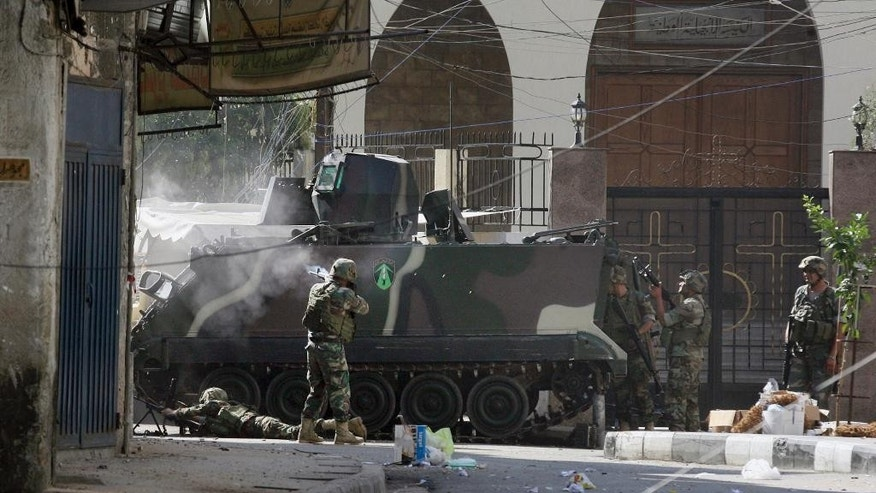 Lebanese army soldiers open fire during clashes with Islamic militants in the northern port city of Tripoli, Lebanon, Saturday, Oct. 25, 2014. Lebanese troops battled Islamic militants in Tripoli for a second day Saturday, with at least one person killed and a dozen people wounded in the clashes, the Lebanese army and state media said. (AP Photo)