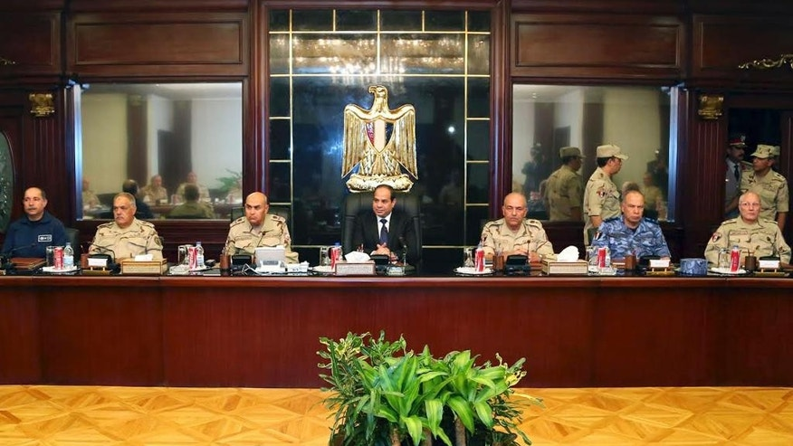 """In this photo provided by Egypt's state news agency MENA, Egyptian President Abdel-Fattah el-Sissi, center, meets with top officials and army commanders in an emergency session in Cairo, Egypt, Saturday, Oct. 25, 2014. El-Sissi appeared on the state-run TV and said a deadly assault on an army checkpoint in the Sinai Peninsula that killed 30 troops was a """"foreign-funded operation."""" No group has yet claimed responsibility for the attack. (AP Photo/MENA)"""