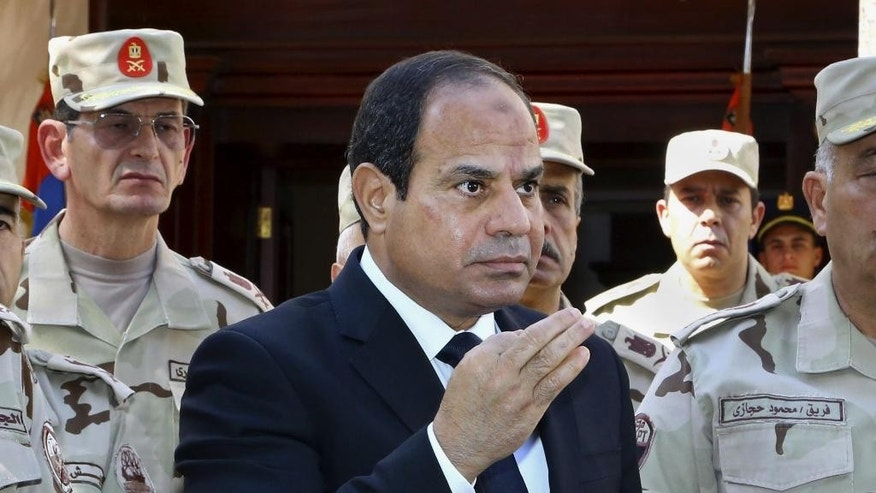 """In this photo provided by Egypt's state news agency MENA, Egyptian President Abdel-Fattah el-Sissi speaks in front of the state-run TV ahead of a military funeral for troops killed in an assault in the Sinai Peninsula, as he stands with army commanders in Cairo, Egypt, Saturday, Oct. 25, 2014. El-Sissi said the deadly assault on an army checkpoint in northern Sinai that killed at least 30 troops was a """"foreign-funded operation."""" No group has yet claimed responsibility for the attack. (AP Photo/MENA, Mohammed Samaha)"""