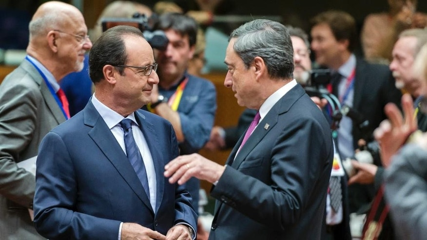 French President Francois Hollande, left, speaks with European Central Bank Governor Mario Draghi, right, during a round table meeting at an EU summit in Brussels on Friday, Oct. 24, 2014. Britain says its prime minister, David Cameron, is protesting a European Union request for an additional 2.1 billion euro ($2.65 billion) contribution to the EU coffers at a time of increasing pressure at home for the country to leave the bloc. (AP Photo/Geert Vanden Wijngaert)