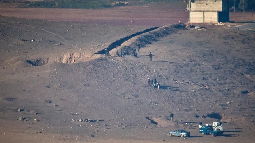 People clear an area, previously controlled by Islamic State fighters, that was hit by an airstrike the day before, craters visible top left, west of Kobani, Syria, as seen from a hilltop on the outskirts of Suruc, near the Turkey-Syria border, Friday, Oct. 24, 2014. Kobani, also known as Ayn Arab, and its surrounding areas, has been under assault by extremists of the Islamic State group since mid-September and is being defended by Kurdish fighters. (AP Photo/Vadim Ghirda)