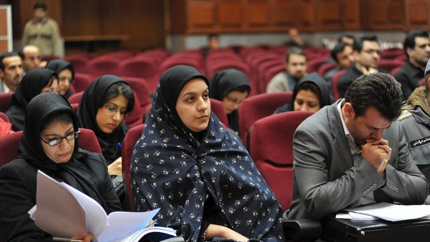 In this picture taken on Dec. 15, 2008, Iranian Reyhaneh Jabbari, center, sits while attending her trial in a court in Tehran, Iran. Jabbari was hanged on Saturday, Oct. 25, 2014, who was convicted of murdering a man she said was trying to rape her, the official IRNA news agency reported. (AP Photo/Golara Sajjadian)