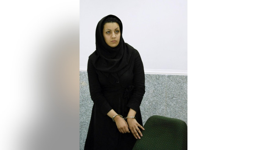 In this picture taken on July 8, 2007, Iranian Reyhaneh Jabbari stands handcuffed in a police office in Tehran, Iran. Jabbari was hanged on Saturday, Oct. 25, 2014, who was convicted of murdering a man she said was trying to rape her, the official IRNA news agency reported. (AP Photo/Golara Sajjadian)