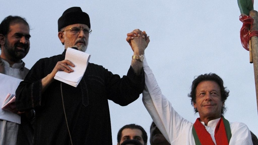 "FILE - In this Tuesday, Sept. 2, 2014 file photo, Pakistan's fiery cleric Tahir-ul-Qadri, second left, and cricketer-turned-politician Imran Khan, right, jointly raise their hands for their supporters during a protest near Prime Minister's home in Islamabad, Pakistan. It had all the elements of a classic coup: thousands descending on the capital, clashing with police outside parliament and commandeering state TV to demand the ouster of a civilian leader who had locked horns with the military in a country with a long history of turmoil and dictatorship. But when the tear gas cleared in Islamabad in August, Pakistan's Prime Minister Nawaz Sharif remained in office with the support of the entire parliament, the troops were still in their barracks, and the protesters had dwindled to a few thousand, their ""revolution"" confined to a festive, shrinking tent camp.  (AP Photo/Anjum Naveed, File)"