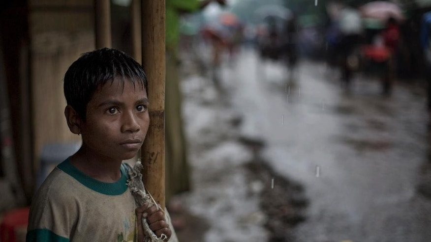 In this June 26 2014 photo, a Rohingya boy who recovers sellable items from garbage dumps, takes shelter in a roadside shop in the rain at The Chaung village north of Sittwe, Rakhine State, Myanmar. A growing sense of desperation is fueling a mass exodus of Rohingya Muslims from western Myanmar, with at least 8,000 members of the long-persecuted minority fleeing by boat in the last two weeks, according to an expert. (AP Photo/Gemunu Amarasinghe)