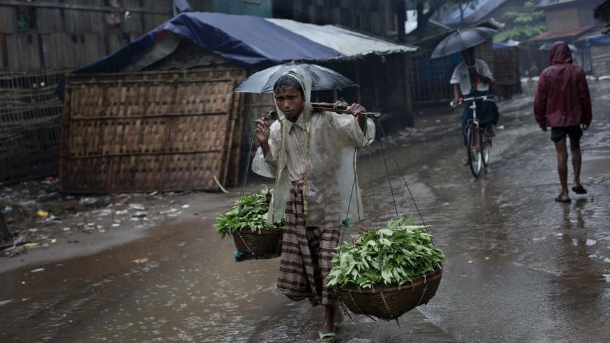 In this June 26, 2014 photo, Rohingya man carries vegetables in the rain at The Chaung village, north of Sittwe, Rakhine State, Myanmar. A growing sense of desperation is fueling a mass exodus of Rohingya Muslims from western Myanmar, with at least 8,000 members of the long-persecuted minority fleeing by boat in the last two weeks, according to an expert. (AP Photo/Gemunu Amarasinghe)