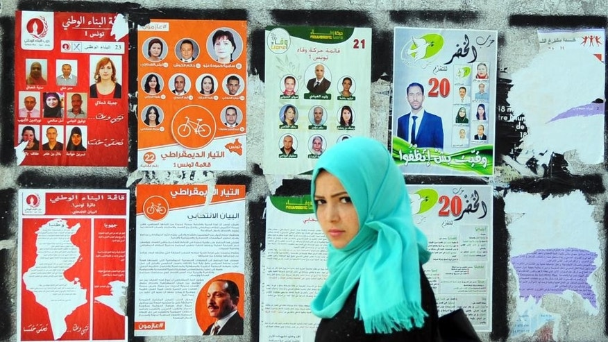 A woman walk past electoral campaign posters for the upcoming parliamentary elections in Tunis, Tunisia, Thursday, Oct. 23, 2014. Tunisians will flock to the polls on Sunday, Oct. 26, 2014, to elect representatives for a four year parliament in one of the final steps for the country's transition to democracy after overthrowing its leader more than three years ago. (AP Photo/Hassene Dridi)