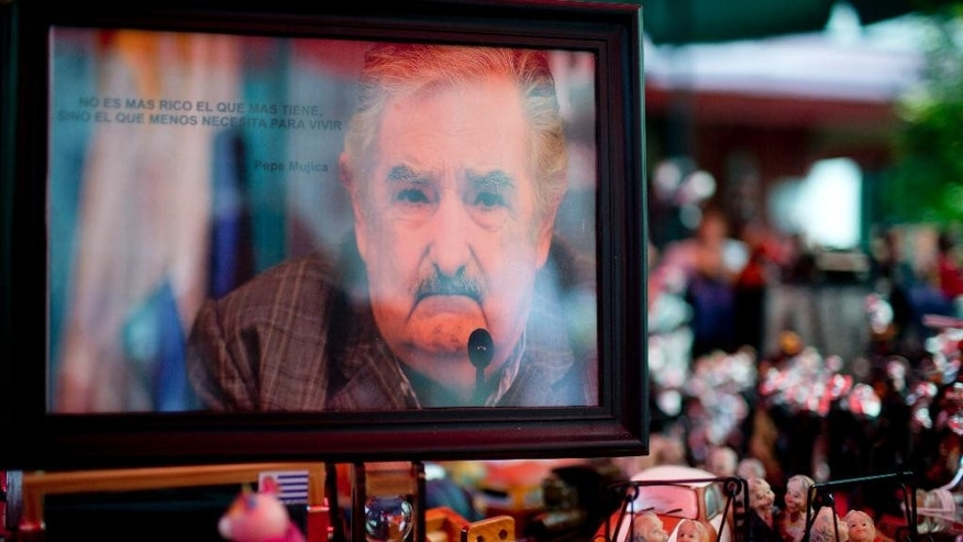 "A portrait of Uruguay's President Jose Mujica, which reads in Spanish ""The richest is not who has the most, its who needs less to live,"" is displayed for sale at a street stand in Montevideo, Uruguay, Friday, Oct. 24, 2014. The political party of outgoing President Jose Mujica, who gained international renown for social reforms such as legalization of marijuana and gay marriage, leads going into Sunday's election to replace him but is far from assured a resounding win. (AP Photo/Natacha Pisarenko)"