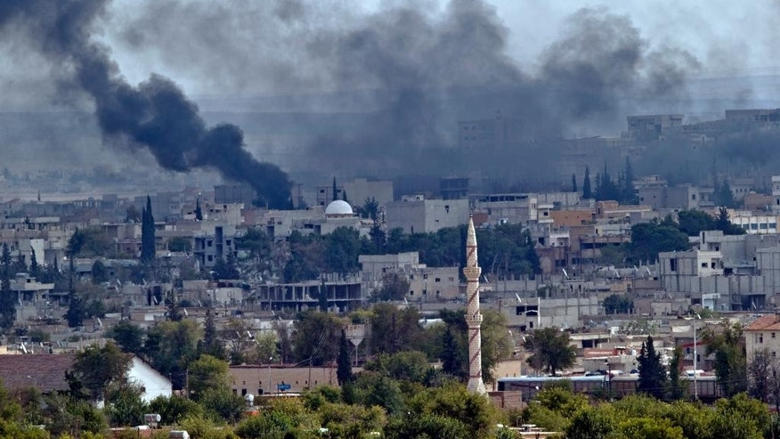 Smoke rises above the Syrian town of Kobani during fighting between Islamic State and Kurdish forces, seen from a hilltop on the outskirts of Suruc, Turkey, near the Turkey-Syria border, Sunday, Oct. 26, 2014. Kobani, also known as Ayn Arab, and its surrounding areas, has been under assault by extremists of the Islamic State group since mid-September and is being defended by Kurdish fighters. (AP Photo/Vadim Ghirda)