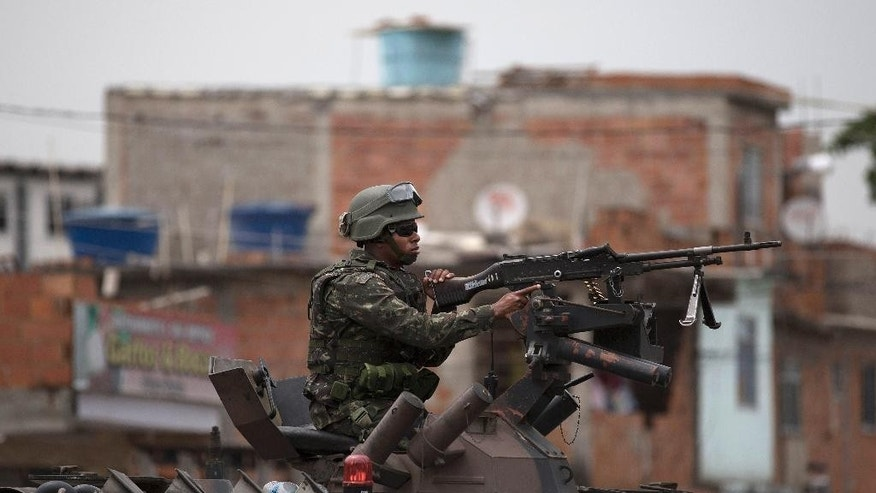 A soldier atop a armored car patrols in the Mare Complex slum ahead of a presidential run-off election Rio de Janeiro, Brazil, Saturday, Oct. 25, 2014. Brazilians will go to the polls on Sunday to decide who'll be the next leader of Latin America's biggest economy. (AP Photo/Leo Correa)